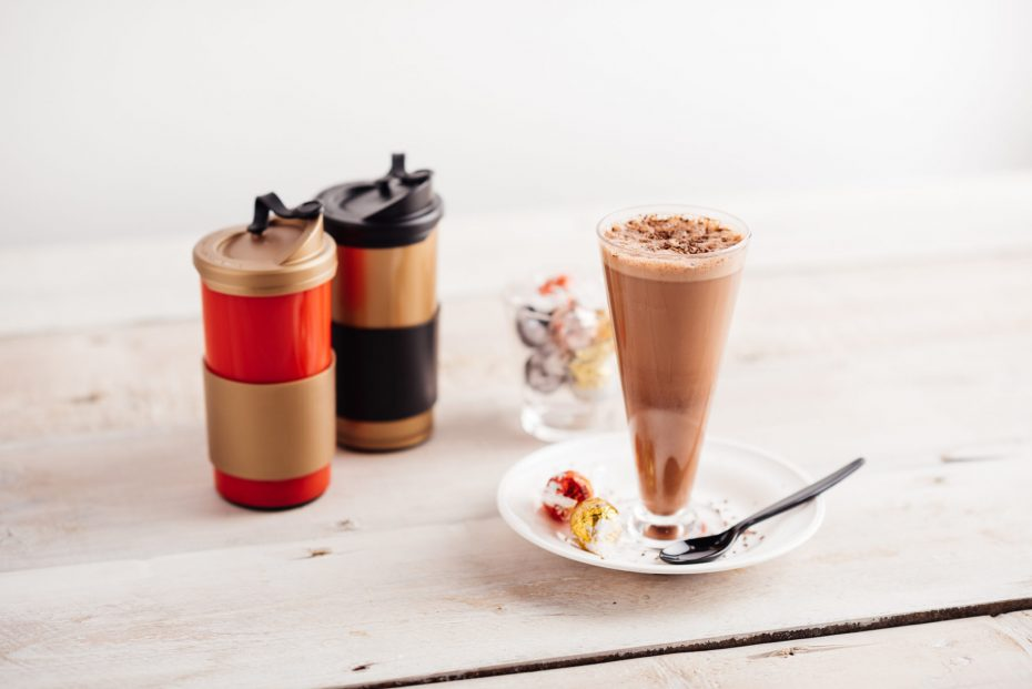 Latte in tall glass and reusable coffee cups