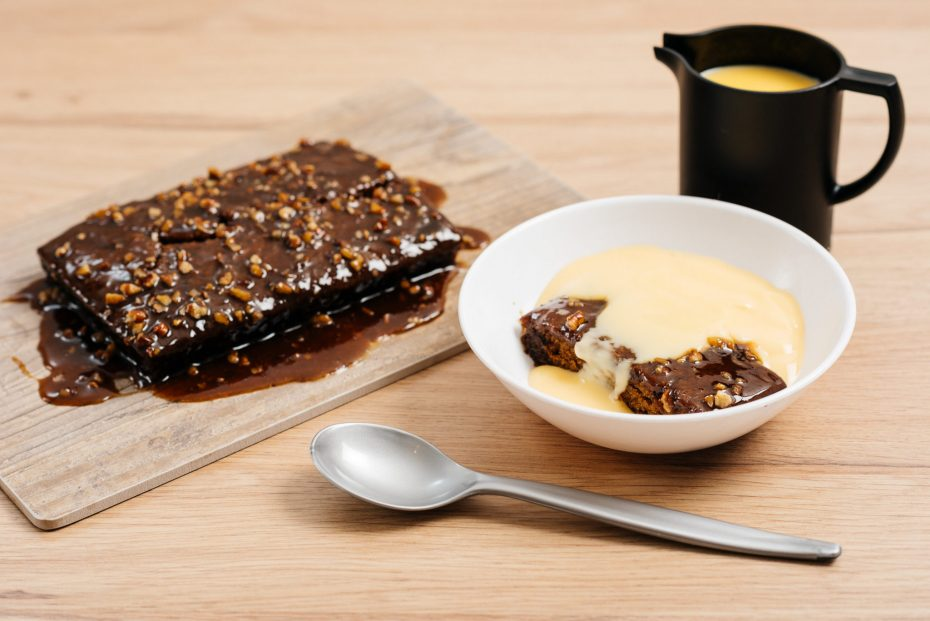 Chocolate Cake with Custard in White Bowl with Black Small Jug