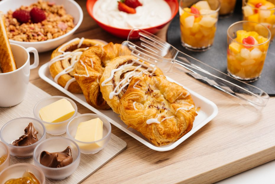 Pastries on white food platter and with serving tongs