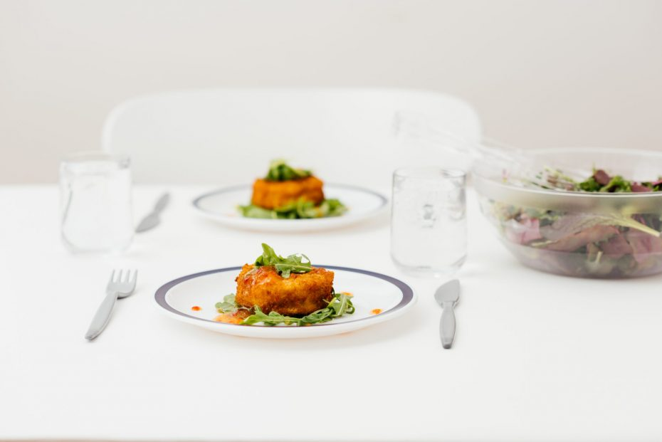 Fishcakes on a white plate with blue band