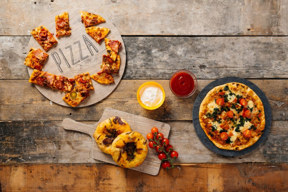 Pizza on a round vintage wood and slate food platters
