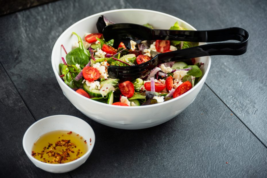Halloumi salad in a white bowl with black serving tongs