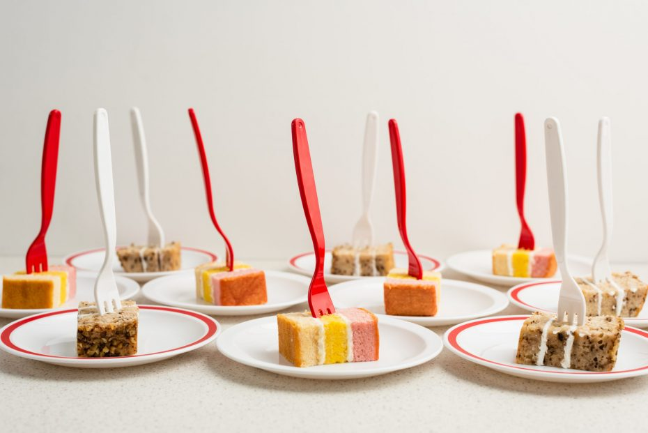 Cakes served on small plates with red and white forks