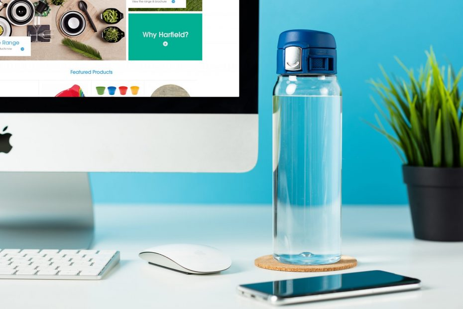 Water Bottle with Blue Sports Cap at a Computer Desk